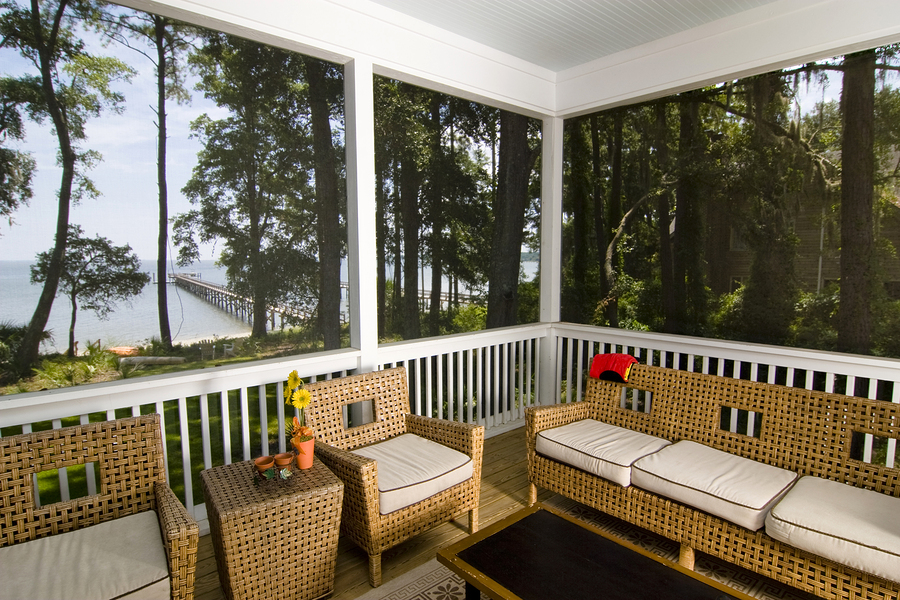 screen porch with beach view and wicker furniture